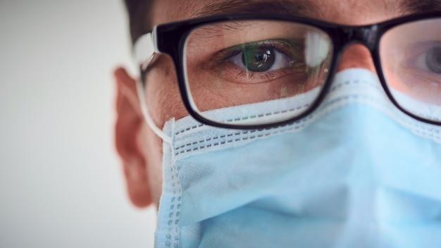 Ritratto del primo piano di giovane medico triste e stanco in vetri appannati e mascherina medica