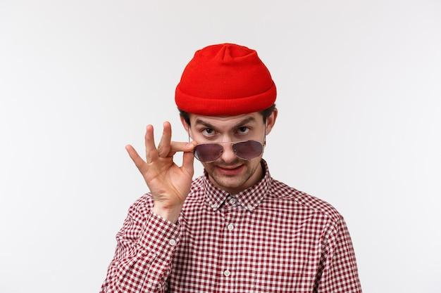 Ritratto del primo piano di giovane ragazzo sospettoso divertente in berretto rosso e camicia a quadri, occhiali da sole da decollo e sguardo da sotto la fronte come spettegolare, accennare o dire segreto, spiare qualcuno