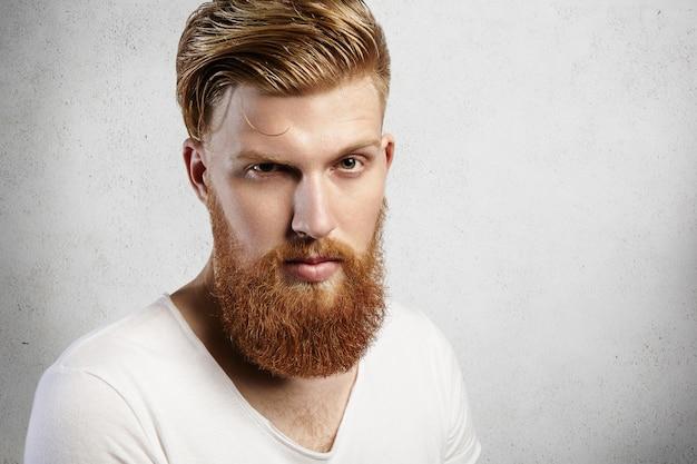 Ritratto del primo piano di giovane uomo caucasico con barba lunga allo zenzero e acconciatura alla moda. il giovane hipster dà uno sguardo indagatore con un sopracciglio alzato. la sua pelle è perfetta e l'espressione riservata.