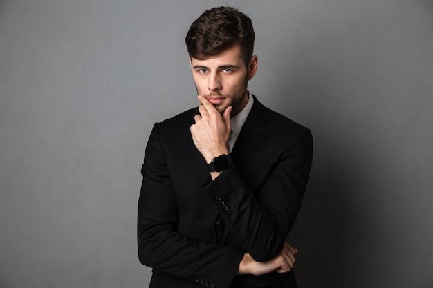 Ritratto del primo piano di giovane uomo d'affari barbuto in vestito nero che tiene il suo mento,
