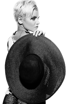 Ritratto del primo piano di look.glamor di alta moda di bello modello caucasico sexy alla moda bello della giovane donna con trucco moderno luminoso con capelli corti con il cappello in mano