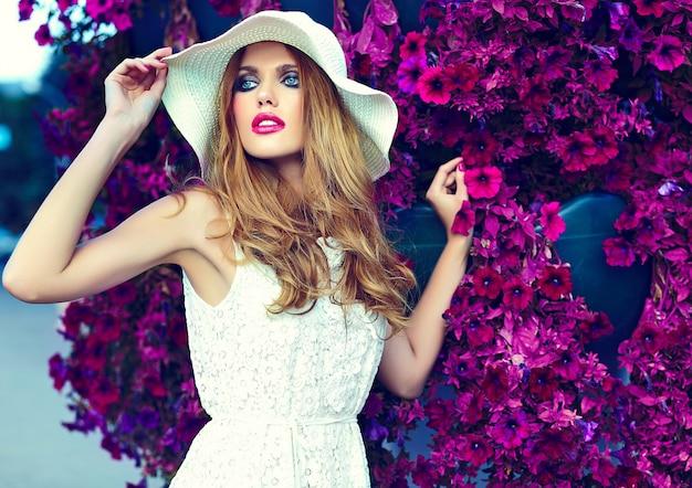 Ritratto del primo piano di look.glamor di alta moda di bello modello di giovane donna bionda alla moda sexy con trucco luminoso e labbra rosa con pelle pulita perfetta in cappello vicino ai fiori di estate