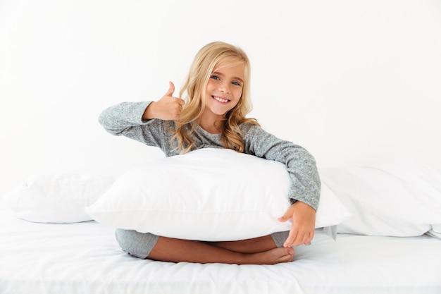 Ritratto del primo piano di piccolo bambino femminile sorridente che si siede con il cuscino bianco a letto, mostrando pollice sul gesto,