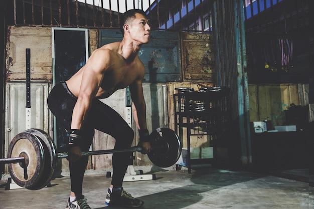 Ritratto del primo piano di un allenamento muscolare dell'uomo con il bilanciere alla palestra locale