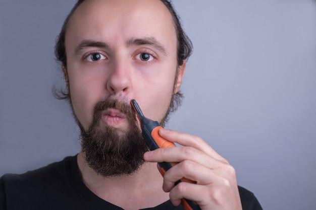 Ritratto del primo piano di un giovane ragazzo utilizzando un rifinitore per baffi. cura di barba e baffi.