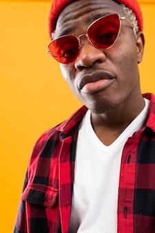 Ritratto del primo piano di un uomo di colore alla moda africano in occhiali retrò rossi e una camicia a quadri e cappello in studio
