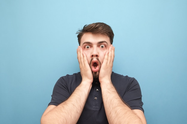 Ritratto del primo piano di un uomo sorpreso che ha preso una mano sulla faccia della paura sull'azzurro