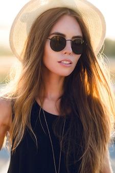 Ritratto del primo piano di una bella ragazza con lunghi capelli scuri che indossa cappello di paglia e occhiali da sole scuri. sorride leggermente