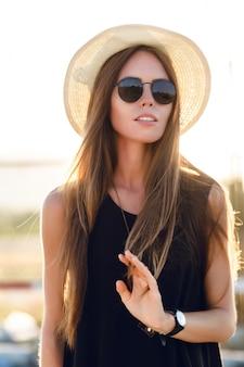 Ritratto del primo piano di una bella ragazza con lunghi capelli scuri che indossa cappello di paglia, occhiali da sole scuri. gioca con i suoi capelli sotto i caldi raggi del sole al tramonto