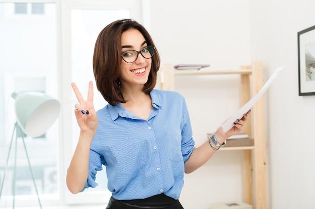 Ritratto del primo piano di una ragazza bruna in camicia blu e gonna nera in piedi in ufficio. tiene la carta in mano. sorride molto felice alla telecamera.
