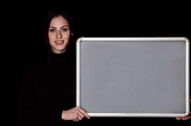 Ritratto del primo piano di una ragazza con colore della pelle chiaro con capelli scuri. ritratto di una ragazza moderna attraente con un aspetto giocoso, su uno sfondo nero. copia spazio