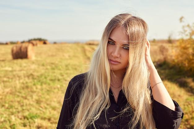 Ritratto del primo piano di una ragazza con i suoi capelli lunghi. la ragazza raddrizza i capelli con una mano, guardando