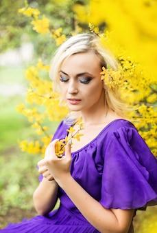Ritratto del primo piano di una ragazza con trucco professionale. bella donna in un vestito viola con fioritura forsizia.