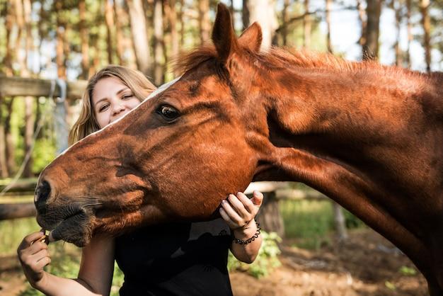 Ritratto del primo piano di una ragazza e di un marrone del cavallo. la donna abbraccia la faccia del cavallo e raggiunge la sua mano. amicizia tra un cavallo e un uomo.