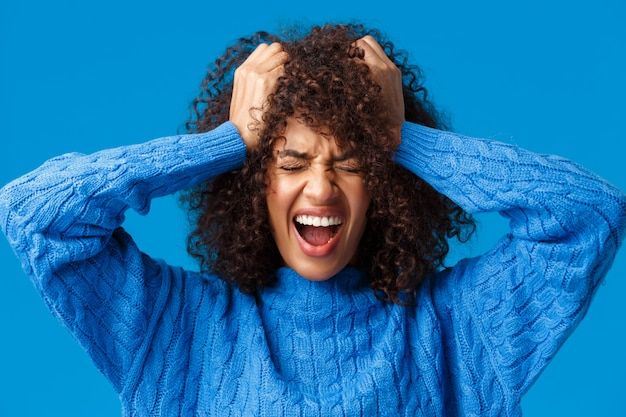 Ritratto del primo piano donna afroamericana turbata angosciata e tesa che grida dal sentirsi a disagio e deluso, in piedi in preda al panico e dispiaciuto per gli occhi chiusi blu che grida