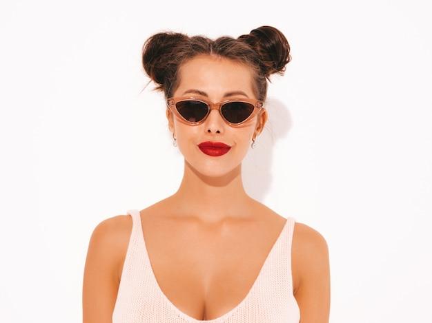 Ritratto del primo piano giovane bella donna sexy dei pantaloni a vita bassa con le labbra rosse in occhiali da sole.