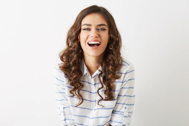 Ritratto del primo piano giovane donna graziosa che ride, espressione emotiva del viso, vestito con una camicia isolato su sfondo bianco, felice, stato d'animo positivo, sorriso sincero, lunghi capelli ricci, denti bianchi