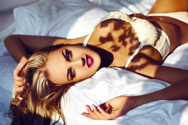 Ritratto del primo piano glamour della bellissima giovane donna elegante elegante modello sdraiato sul letto bianco con trucco luminoso, con labbra rosse, con una pelle pulita perfetta in lingerie bianca