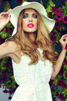 Ritratto del primo piano look.glamor di alta moda di bello modello di giovane donna bionda alla moda sexy con trucco luminoso e labbra rosa con pelle pulita perfetta in cappello vicino ai fiori di estate
