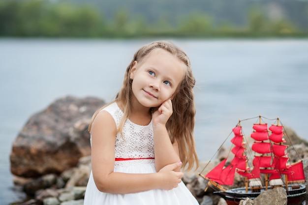 Ritratto del primo piano piccola ragazza sveglia in vestito bianco e vele rosse. bambino seduto sul mare con nave giocattolo.