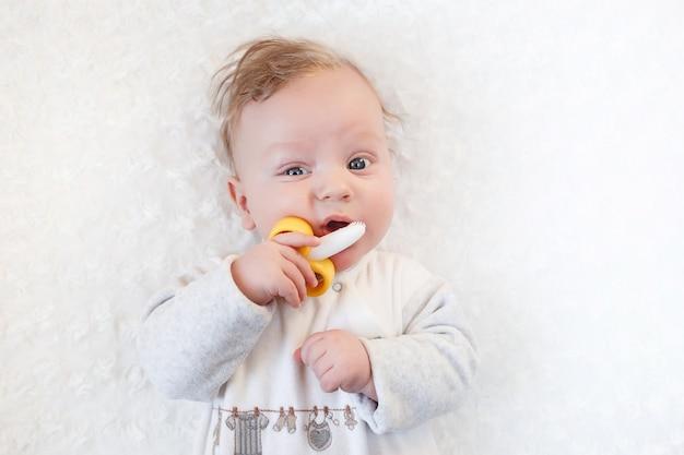 Ritratto del primo piano ragazzino carino con grandi occhi blu con un giocattolo tra le mani, stuzzichini un giocattolo massaggiagengive banana