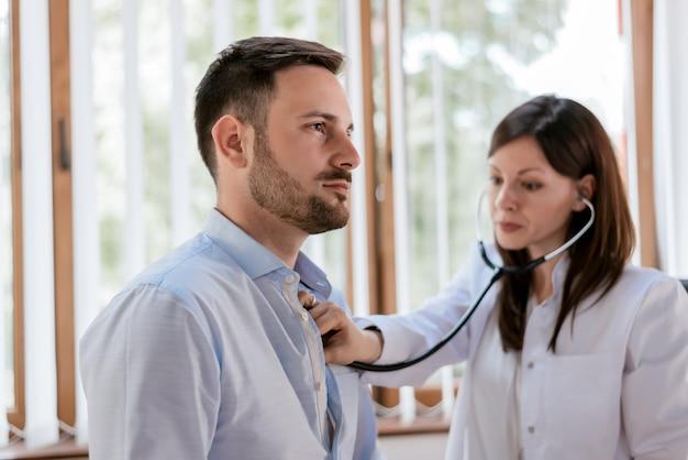 Ritratto del professionista sicuro che controlla battito cardiaco del paziente
