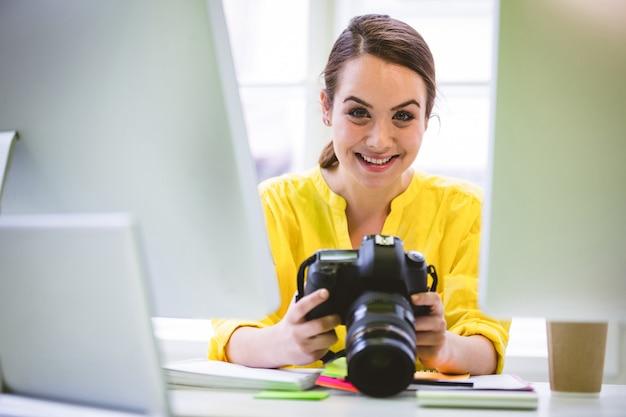 Ritratto del professionista sicuro con la macchina fotografica digitale e il computer all'ufficio