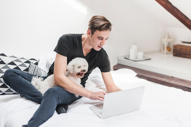 Ritratto del proprietario con il suo cane carino utilizzando il portatile in camera da letto