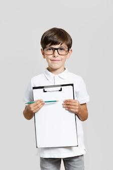 Ritratto del ragazzino che tiene una lavagna per appunti