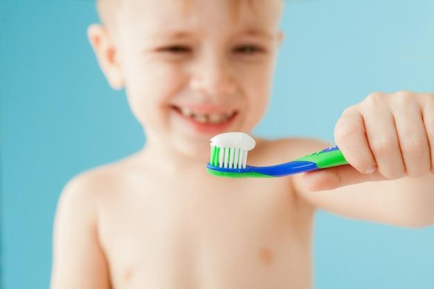 Ritratto del ragazzino con lo spazzolino da denti su fondo blu