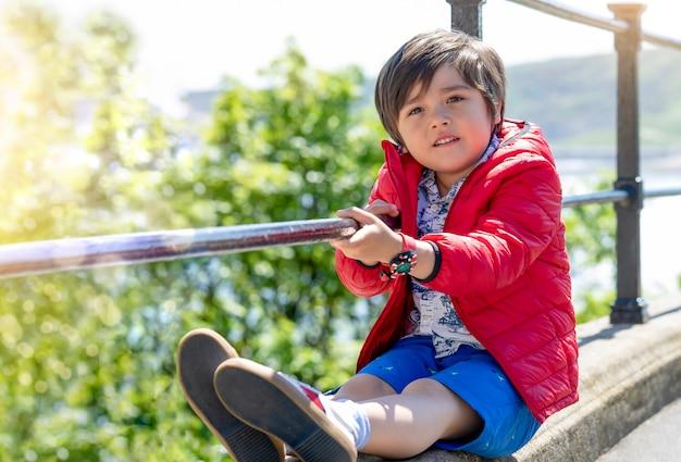 Ritratto del ragazzino con seduta sorridente da solo accanto alla strada, bambino felice che indossa giacca rossa giocando all'aperto in una giornata di sole. sorriso del bambino e guardare fuori, concetto positivo dei bambini