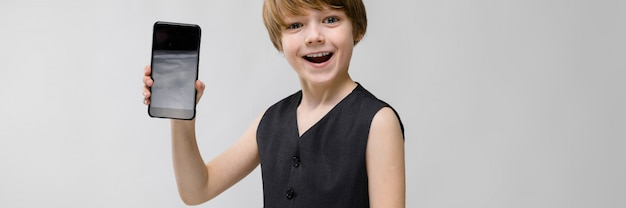 Ritratto del ragazzino divertente adorabile che sta in maglia nera che mostra telefono cellulare
