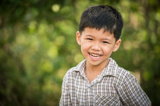 Ritratto del ragazzino felice che ride mentre gioca nel parco.