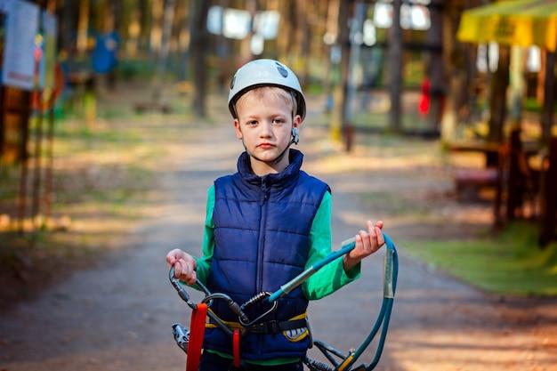 Ritratto del ragazzino felice divertendosi nel parco di avventura che sorride al casco e alle attrezzature di sicurezza d'uso della macchina fotografica.