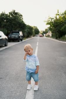 Ritratto del ragazzino sveglio che cammina sulla strada nel suo quartiere