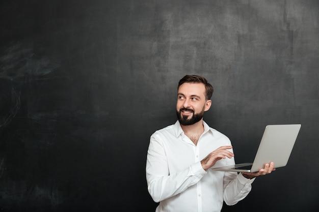 Ritratto del ragazzo adulto sorridente che tiene computer portatile d'argento e che osserva da parte, isolato sopra la parete grigio scuro