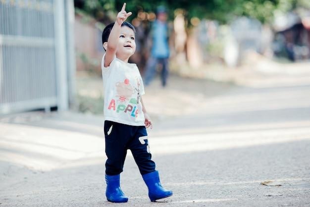 Ritratto del ragazzo asiatico felice all'aperto nell'immagine con lo spazio della copia