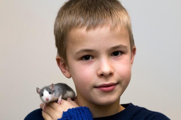 Ritratto del ragazzo bello sveglio divertente divertente sorridente felice con il criceto bianco del topo dell'animale domestico sulla spalla sul fondo leggero dello spazio della copia.