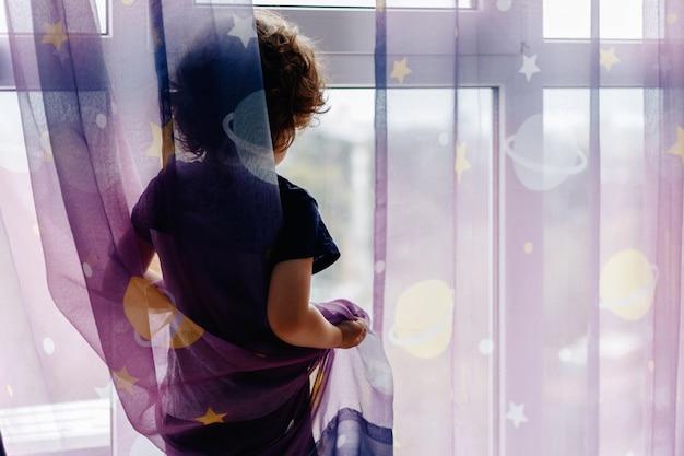 Ritratto del ragazzo caucasico bianco del bambino a casa che guarda dalla finestra fuori. vista dal retro ragazzino in attesa di qualcuno