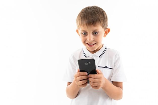 Ritratto del ragazzo caucasico felice che chiacchiera con i suoi amici o che gioca i giochi e i sorrisi del telefono