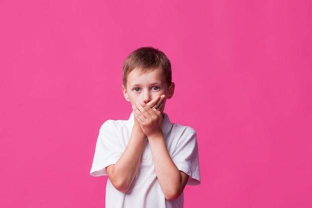 Ritratto del ragazzo che copre la sua bocca su fondo rosa
