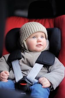 Ritratto del ragazzo del bambino che si siede nella sede di automobile