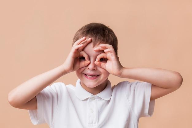 Ritratto del ragazzo felice che osserva tramite le dita come binocolo