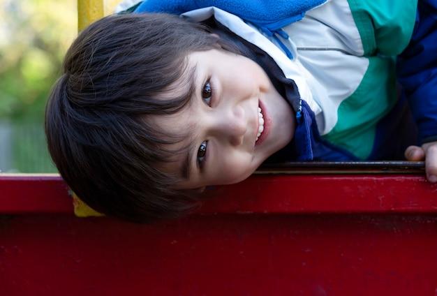 Ritratto del ragazzo felice che sorride con la testa sideway che esamina macchina fotografica