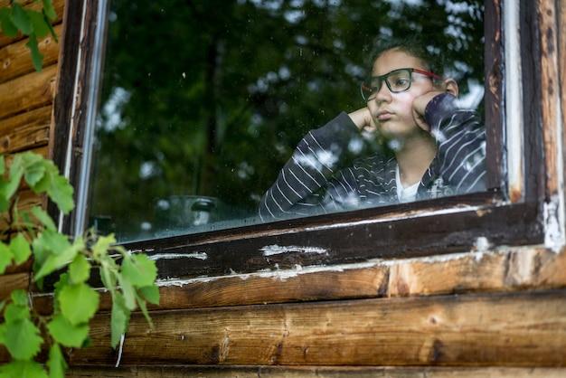 Ritratto del ragazzo guardando attraverso la finestra