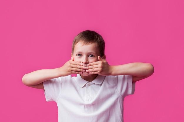 Ritratto del ragazzo innocente che copre la sua bocca e che esamina macchina fotografica sopra il fondo rosa della parete