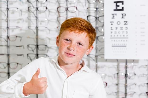 Ritratto del ragazzo sorridente che mostra pollice sul gesto che esamina macchina fotografica