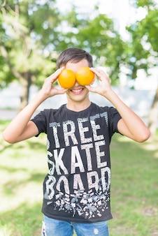 Ritratto del ragazzo sorridente che tiene le intere arance fresche sopra lei occhi nel parco