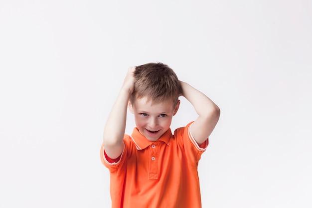 Ritratto del ragazzo sveglio innocente che controlla parete bianca