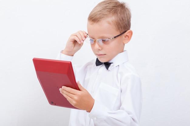Ritratto del ragazzo teenager con il calcolatore su bianco